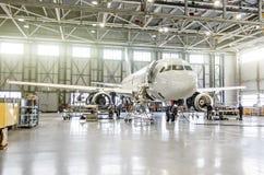 Avions de transport de passagers sur l'entretien de la réparation de moteur et de fuselage dans le hangar d'aéroport Images libres de droits