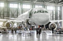 Avions de transport de passagers sur l'entretien de la réparation de moteur et de fuselage dans le hangar d'aéroport Photos stock