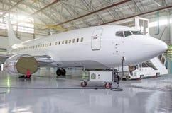 Avions de transport de passagers sur l'entretien de la réparation de moteur et de fuselage dans le hangar d'aéroport Photo libre de droits