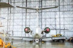 Avions de transport de passagers sur l'entretien de la réparation de moteur et de fuselage dans le hangar d'aéroport Vue arrière  Photographie stock