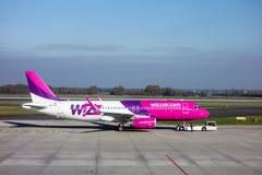 Avions de Wizzair remorqués en le camion de service Photographie stock