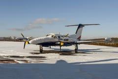 Avions jumeaux de moteur avec la centrale de turbopropulseur sous la neige dans le jour d'hiver ensoleillé Images libres de droits