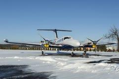 Avions jumeaux de moteur avec la centrale de turbopropulseur sous la neige dans le jour d'hiver ensoleillé Photos libres de droits
