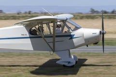 Avions légers spéciaux de moteur simple du joueur de pipeau PA-11 CUB décollant d'un aérodrome de pays images stock