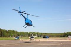 Avions - Robinson bleu et petits hélicoptères S russe de stationnement Image libre de droits