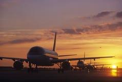 Avions se reposant sur le macadam au coucher du soleil image stock