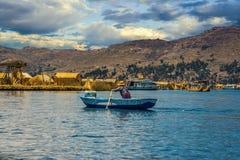 Aviron de femme sur un bateau, île d'Uros, lac Titicaca, Pérou images libres de droits