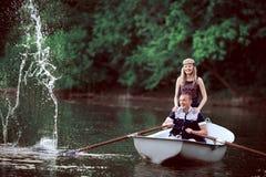 Aviron heureux de couples et éclaboussement sur le lac Image stock