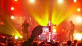 Avive a la persona que toma el vídeo y las fotos en smartphone móvil en el partido del concierto en la iluminación del proyector almacen de metraje de vídeo