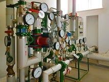Avkännare och apparater som indikerar parametrarna av varmvatten i uppvärmningsystemet av ett stort hus Fläta samman av rör tekni arkivfoto
