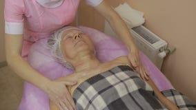 Avkopplad äldre kvinna som får brunnsortmassage arkivfilmer