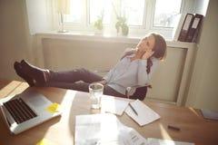 Avkopplad affärskvinna med ben på skrivbordet Royaltyfri Bild
