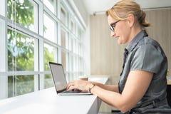 Avkopplad affärskvinna som ler och arbetar på bärbar datordatoren arkivfoton