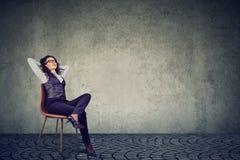 Avkopplad affärskvinna som vilar på stol arkivbild