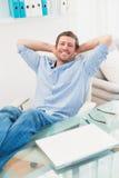 Avkopplad affärsman med hans fot upp Arkivbild