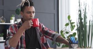 Avkopplad affärsman som dricker kaffe på kontoret arkivfilmer