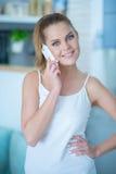 Avkopplad attraktiv kvinna som använder en mobiltelefon Royaltyfri Foto