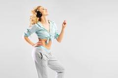 Avkopplad blond kvinna som lyssnar till musik Arkivbild