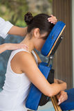 Avkopplad brunett som får en massage i stol Royaltyfri Foto