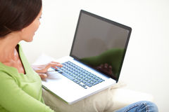 Avkopplad caucasian kvinna som använder en bärbar dator arkivfoto