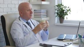 Avkopplad doktor i regeringsställning med kaffe i handen som ser och tänker royaltyfri fotografi