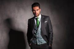 Avkopplad elegant man med händer i fack som bär smokingen arkivfoton