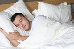 Avkopplad etnisk man som sover som en behandla som ett barn arkivfoto