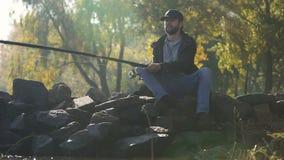 Avkopplad fiskare som tycker om fiska och naturscape som vilar från upptaget liv arkivfilmer