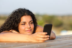 Avkopplad flicka som håller ögonen på socialt massmedia i smart telefon Royaltyfri Foto
