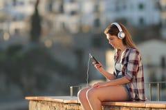 Avkopplad flicka som lyssnar till musik med telefonen på en avsats fotografering för bildbyråer