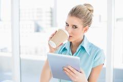 Avkopplad flott kvinna som använder minnestavlan, medan dricka kaffe arkivbilder