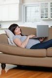 Avkopplad gravid kvinna som använder bärbara datorn Arkivfoton