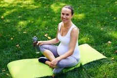 Avkopplad gravid sportive kvinna med flaskan av vattensammanträde in Royaltyfri Bild