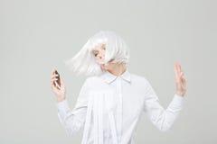 Avkopplad härlig kvinna som lyssnar till musik från smartphonen och att dansa royaltyfri bild