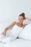 Avkopplad härlig kvinna som sitter på soffan Royaltyfria Bilder