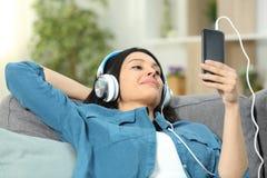 Avkopplad kvinna på en soffa som hemma lyssnar till musik royaltyfri foto