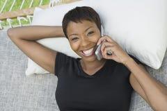 Avkopplad kvinna på hängmattan genom att använda mobiltelefonen Fotografering för Bildbyråer