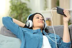 Avkopplad kvinna på hållande ögonen på video för en soffa på telefonen arkivbild