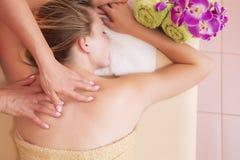 Avkopplad kvinna på massagetabellen som mottar skönhetbehandling på dagbrunnsorten arkivbild