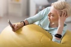 Avkopplad kvinna som använder den smarta telefonen Arkivbilder