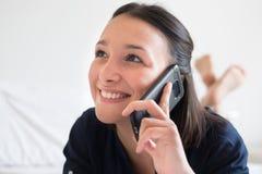 Avkopplad kvinna som använder den smarta telefonen på sängen arkivbilder