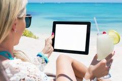 Avkopplad kvinna som dricker coctail- och innehavminnestavladatoren på stranden Fotografering för Bildbyråer