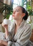 Avkopplad kvinna som dricker te på brunnsortsemesterorten Royaltyfria Bilder