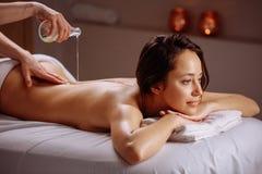 Avkopplad kvinna som har massage med olja i brunnsort Arkivbilder