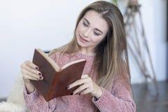 Avkopplad kvinna som hemma läser en bok på en soffa arkivbilder