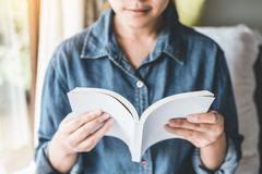 Avkopplad kvinna som läser en bok på säng i morgonen, ferie Tid royaltyfria bilder