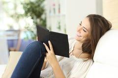 Avkopplad kvinna som läser en ebook arkivbilder