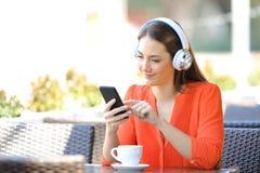 Avkopplad kvinna som lyssnar till musik i en coffee shop royaltyfria bilder