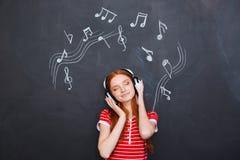 Avkopplad kvinna som lyssnar till musik i hörlurar över svart tavlabakgrund royaltyfri foto