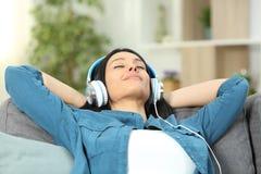 Avkopplad kvinna som vilar att lyssna till musik på en soffa arkivbild